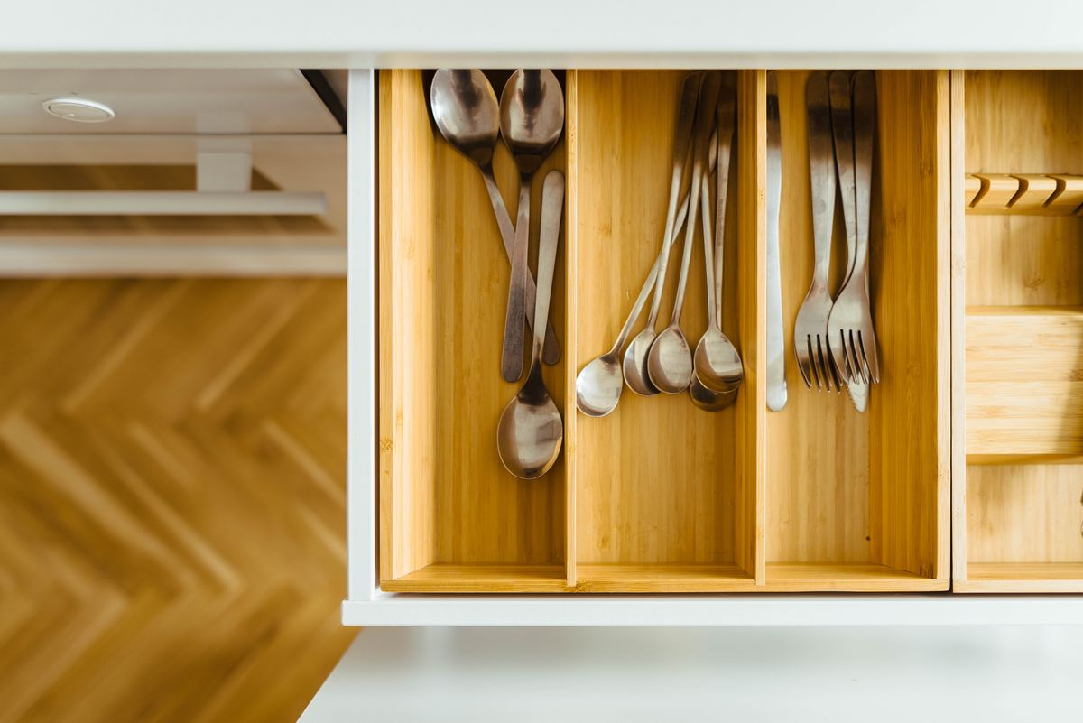 Silverware rests in a wooden drawer