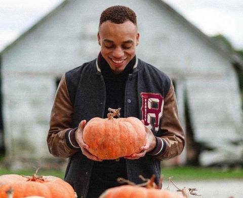 Man holds a pumpkin in a pumpkin patch in Chicago, Illinois