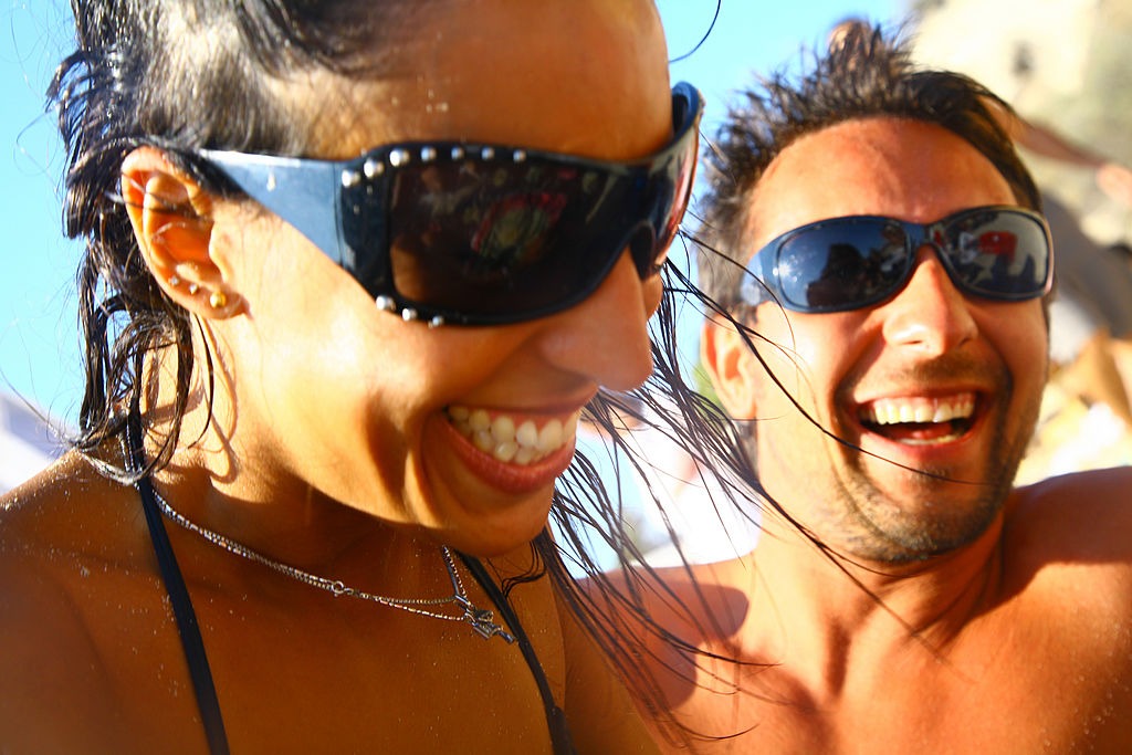 An attractive young couple laughing together on the beach,