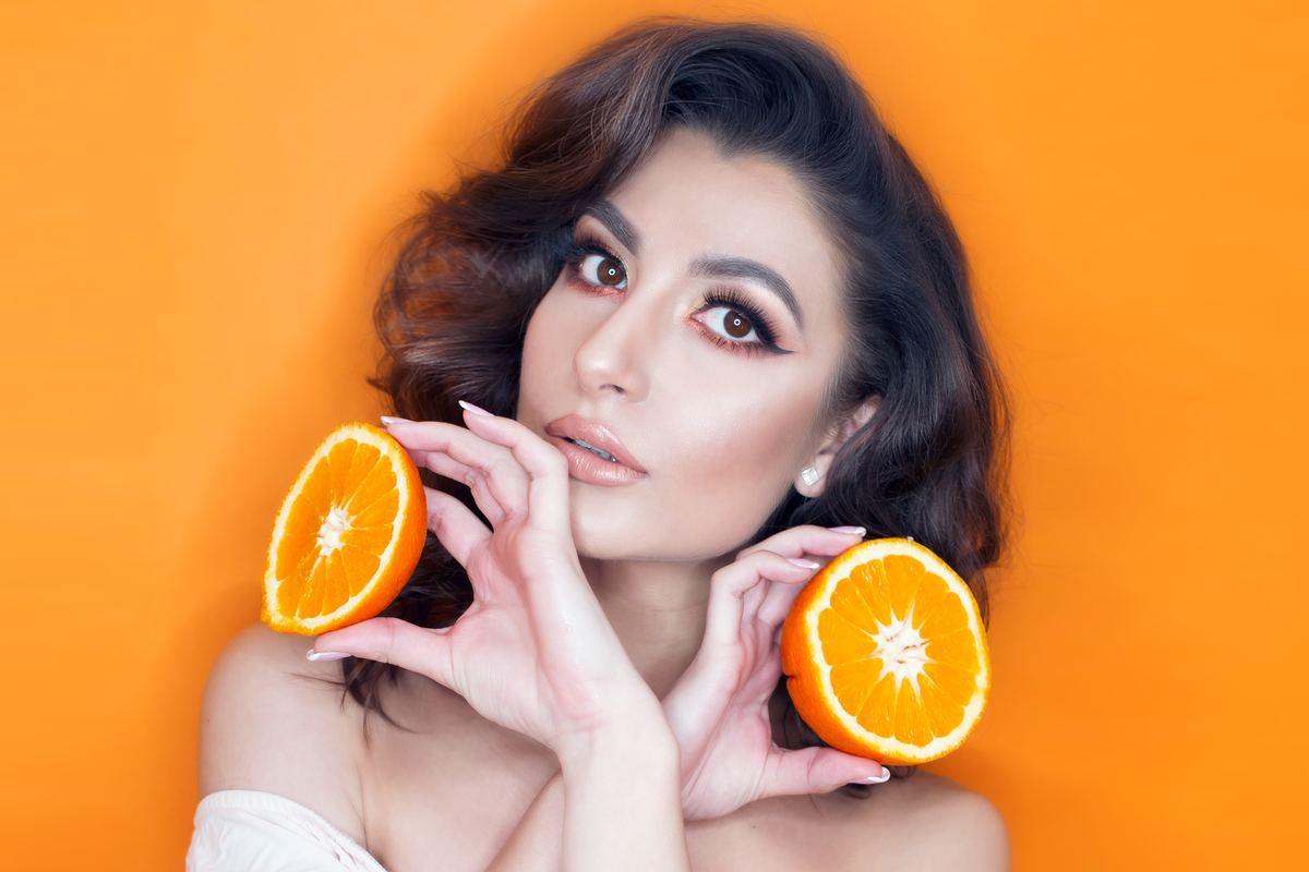 Model holds a sliced orange in front of an orange background