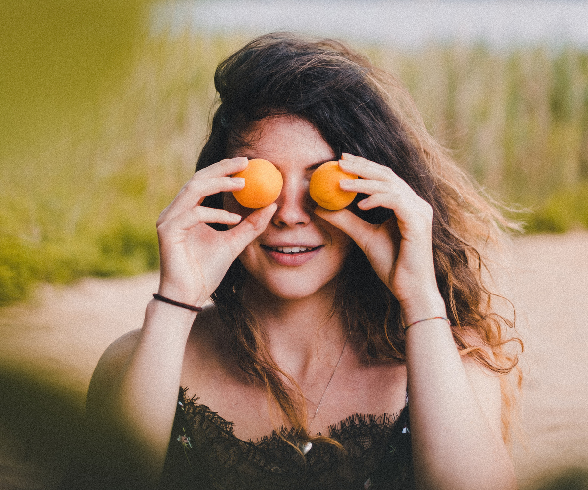 Woman holds orange persimmons over her eyes