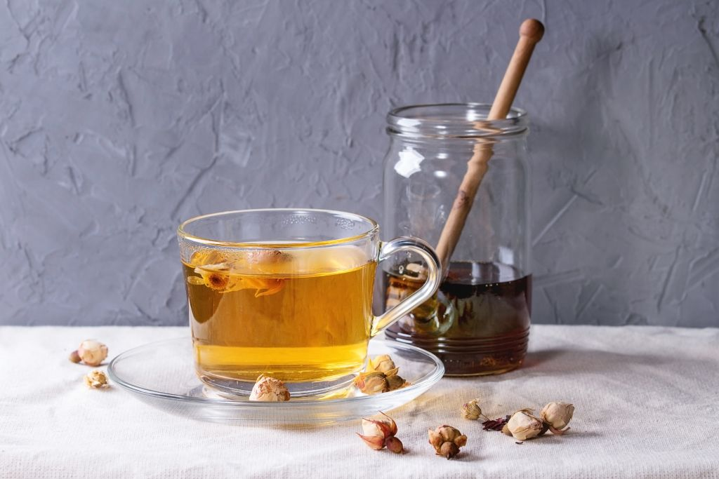 Glass cup of hot herbal tea with dry roses buds, served with glass jar of honey and honey dipper