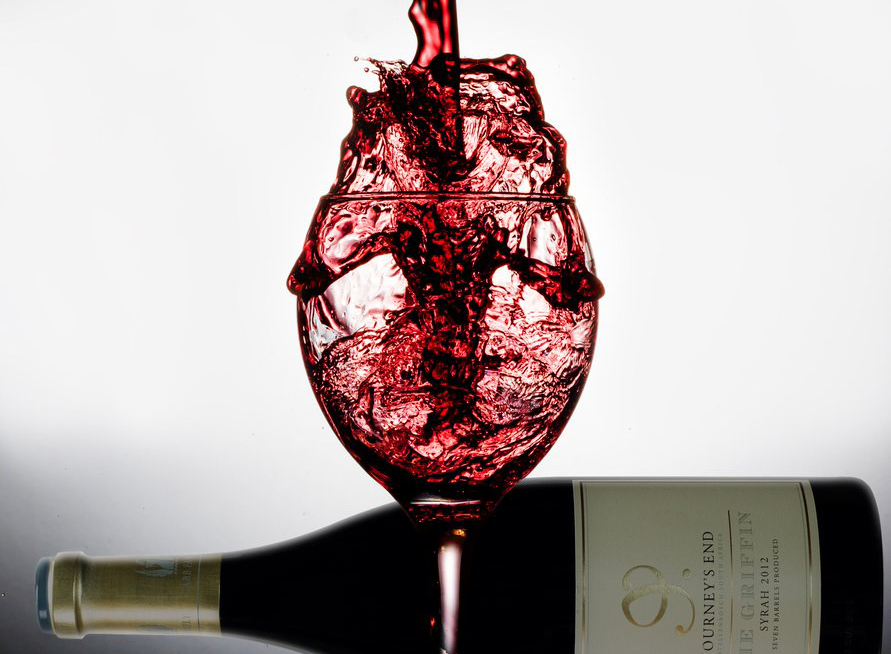 Red wine called The Griffin pours unsteadily into a wine glass