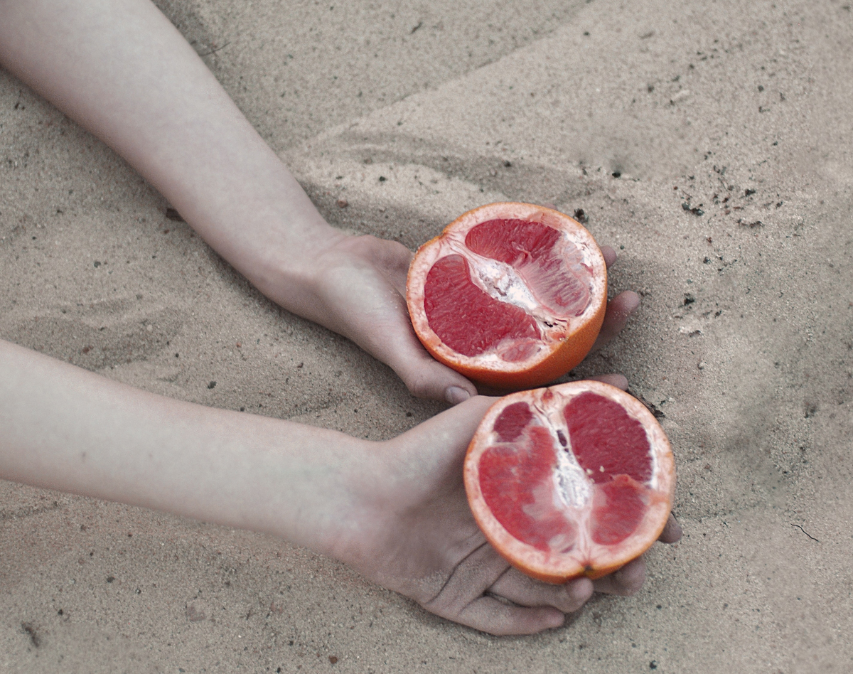 Person holds sliced grapefruit in the sand
