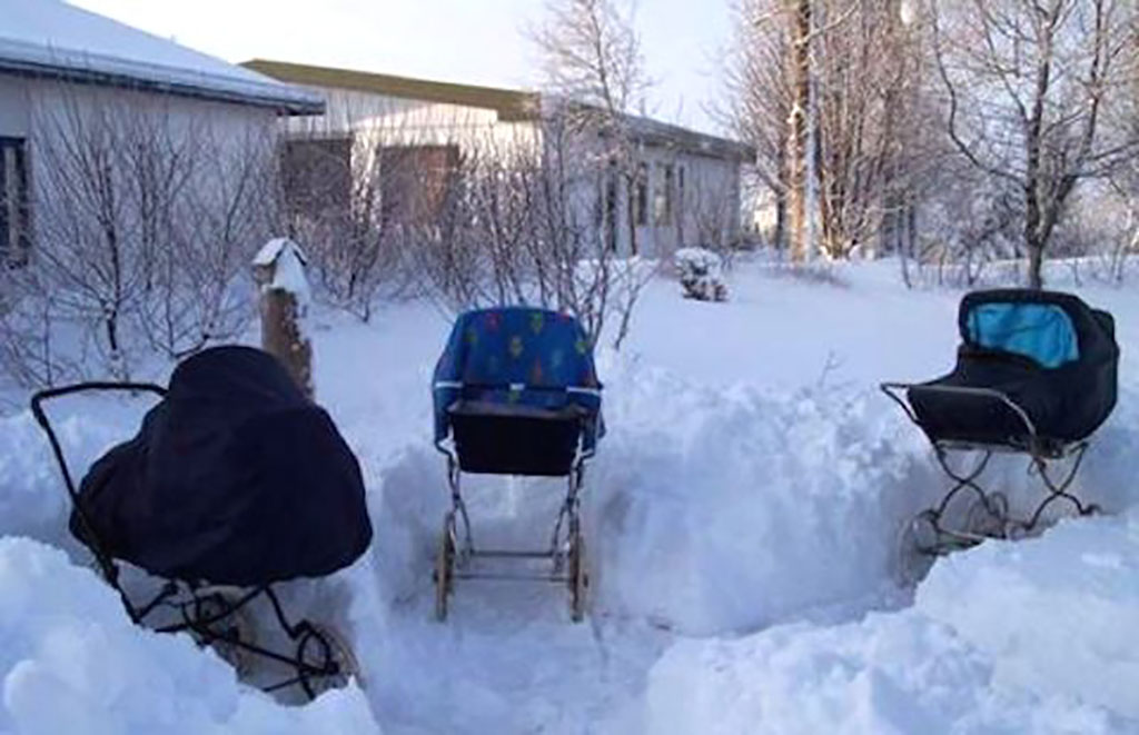 Three abandoned strollers sit in a front yard thick with feet of snow