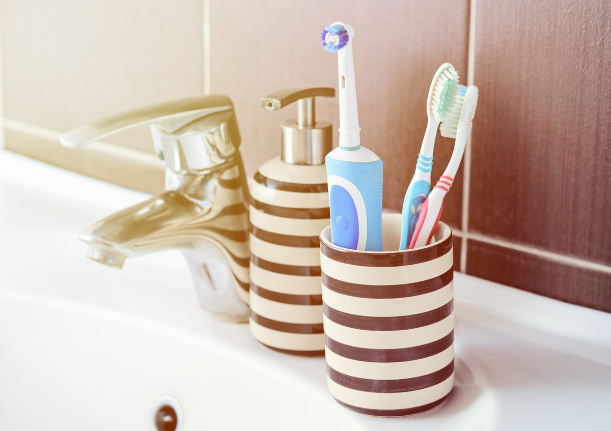 Toothbrushes in a container on the bathroom sink