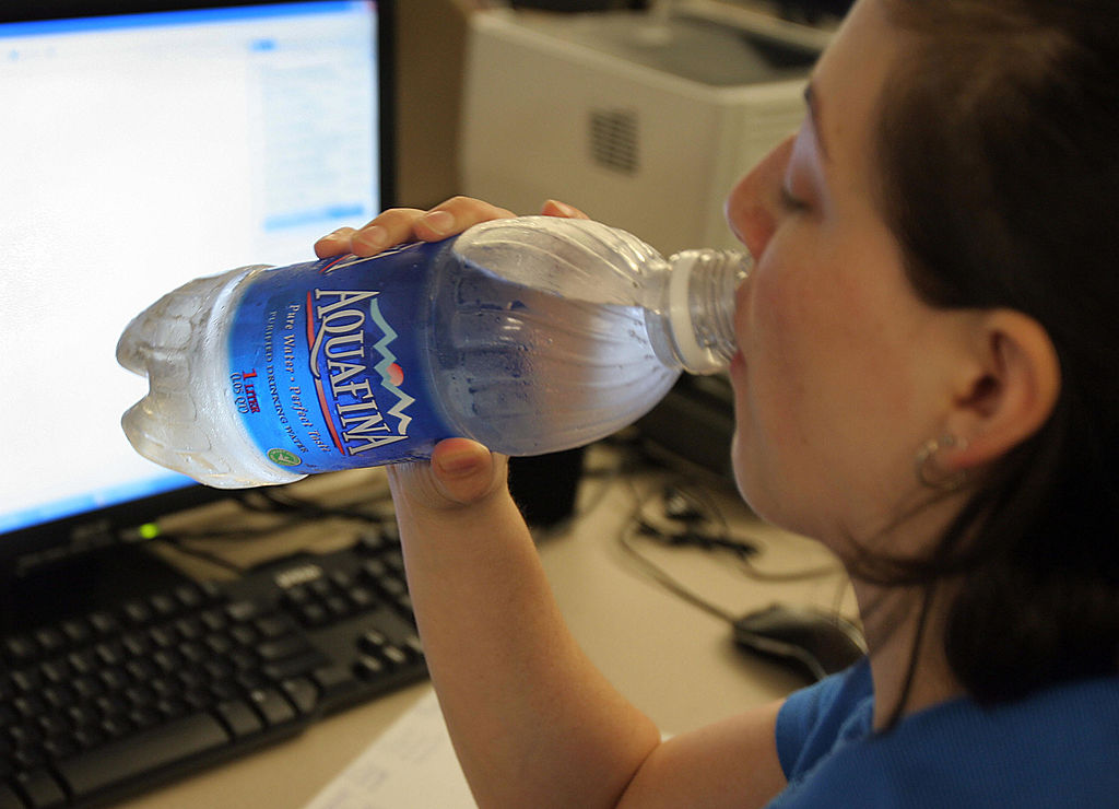 a woman drinking bottled water.
