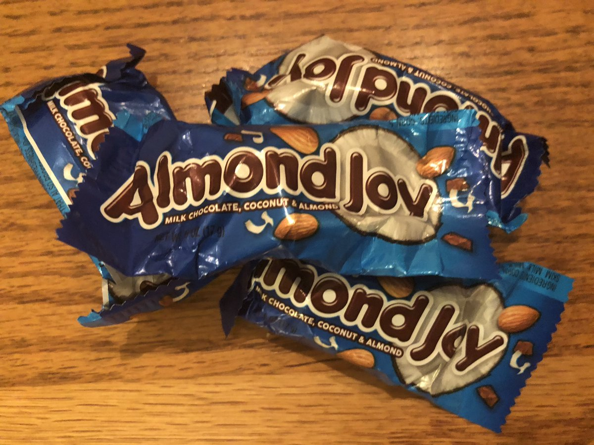 Almond Joy wrappers lay scattered on a wooden table.