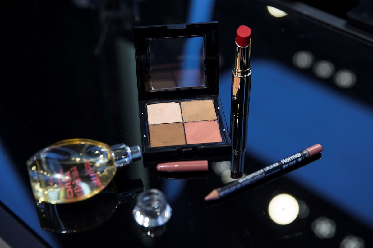 A photo shows the close-up of a various types of eye shadows, perfume bottle, highlighter, lipstick and lip liner