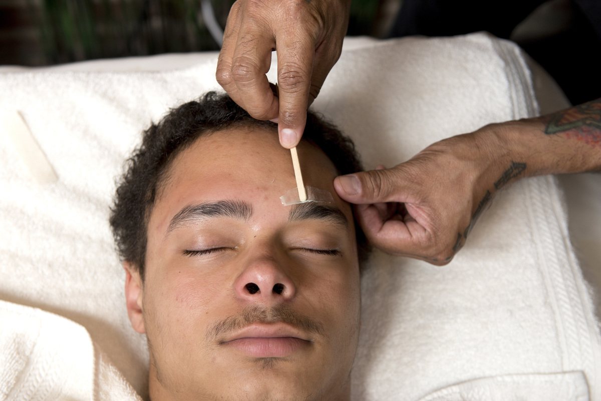 Man closes his eyes as someone places wax above his eyebrows.