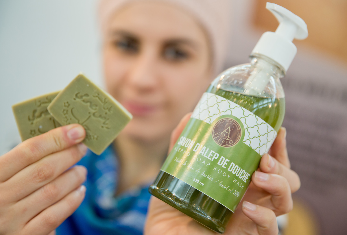 Woman holds up organic soap by Syrian company.