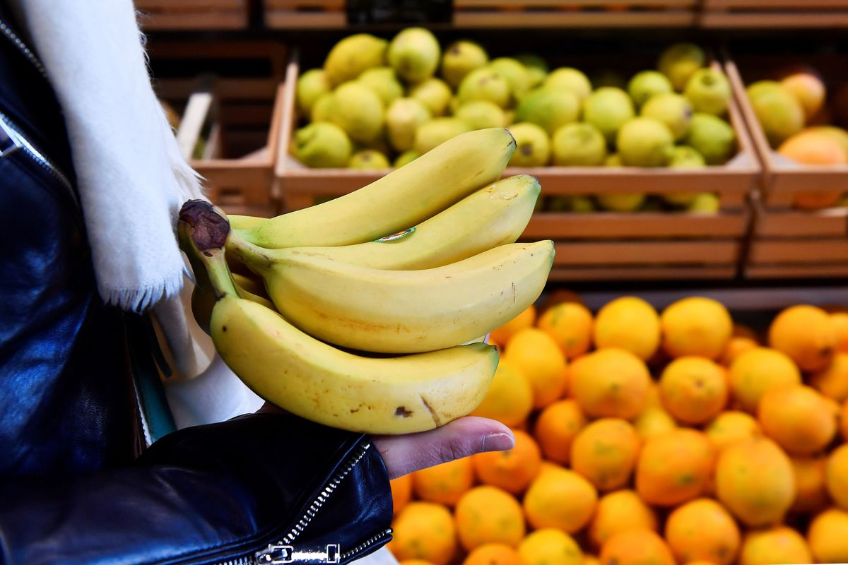 A customer holds bananas in front of a fruit shelf in an organic supermarket