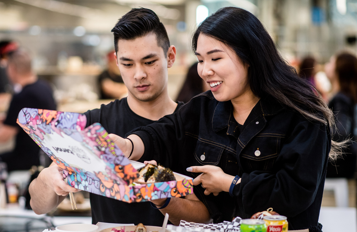 Lifestyle blogger Connie Yang with friend, Jeff Zhang, sample musubi, a popular Japanese rice snack
