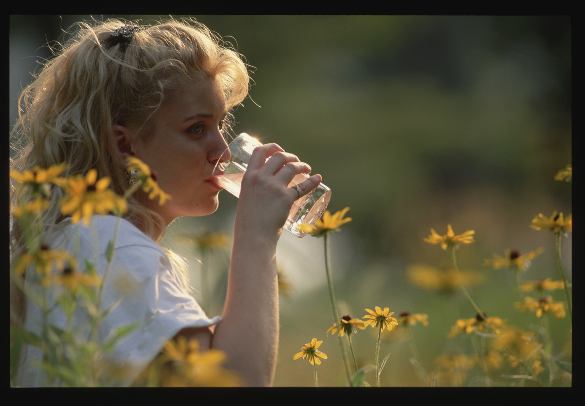 A young woman sits amid black-eyed susans and drinks a glass of water.