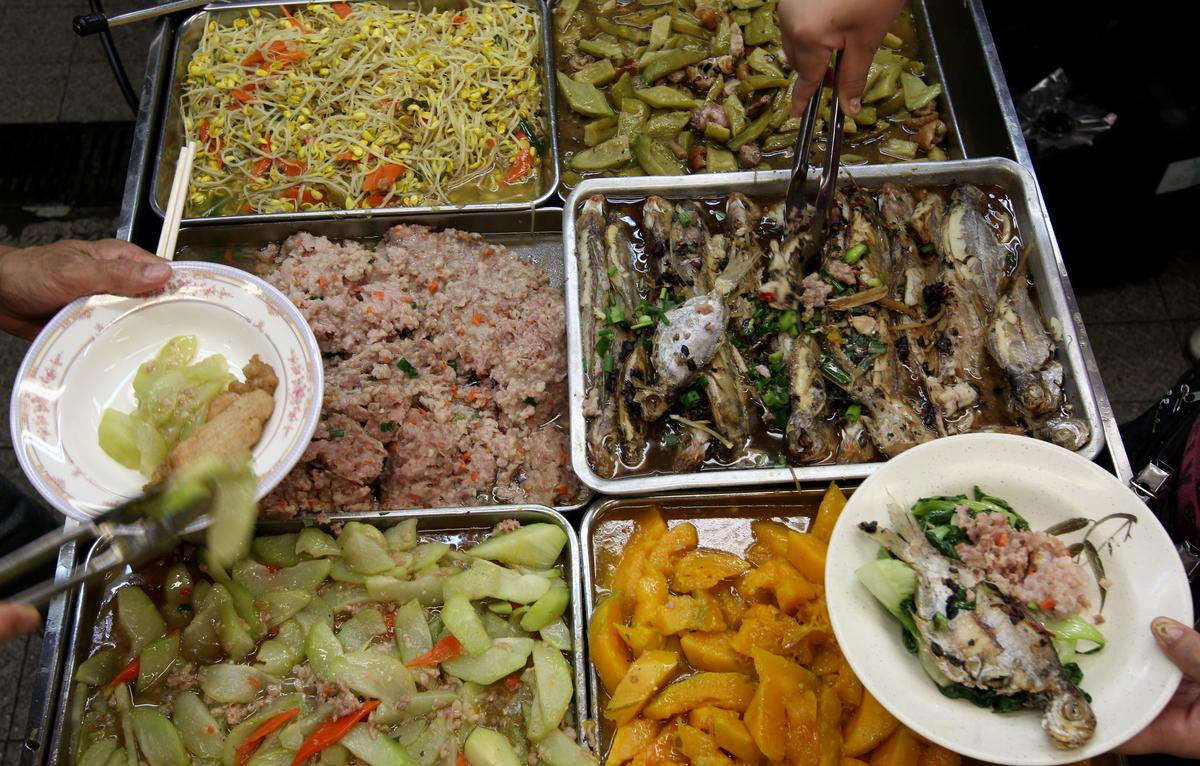 Customers grab food at a 20-dollar buffet food stall at Choi Hung Road Market