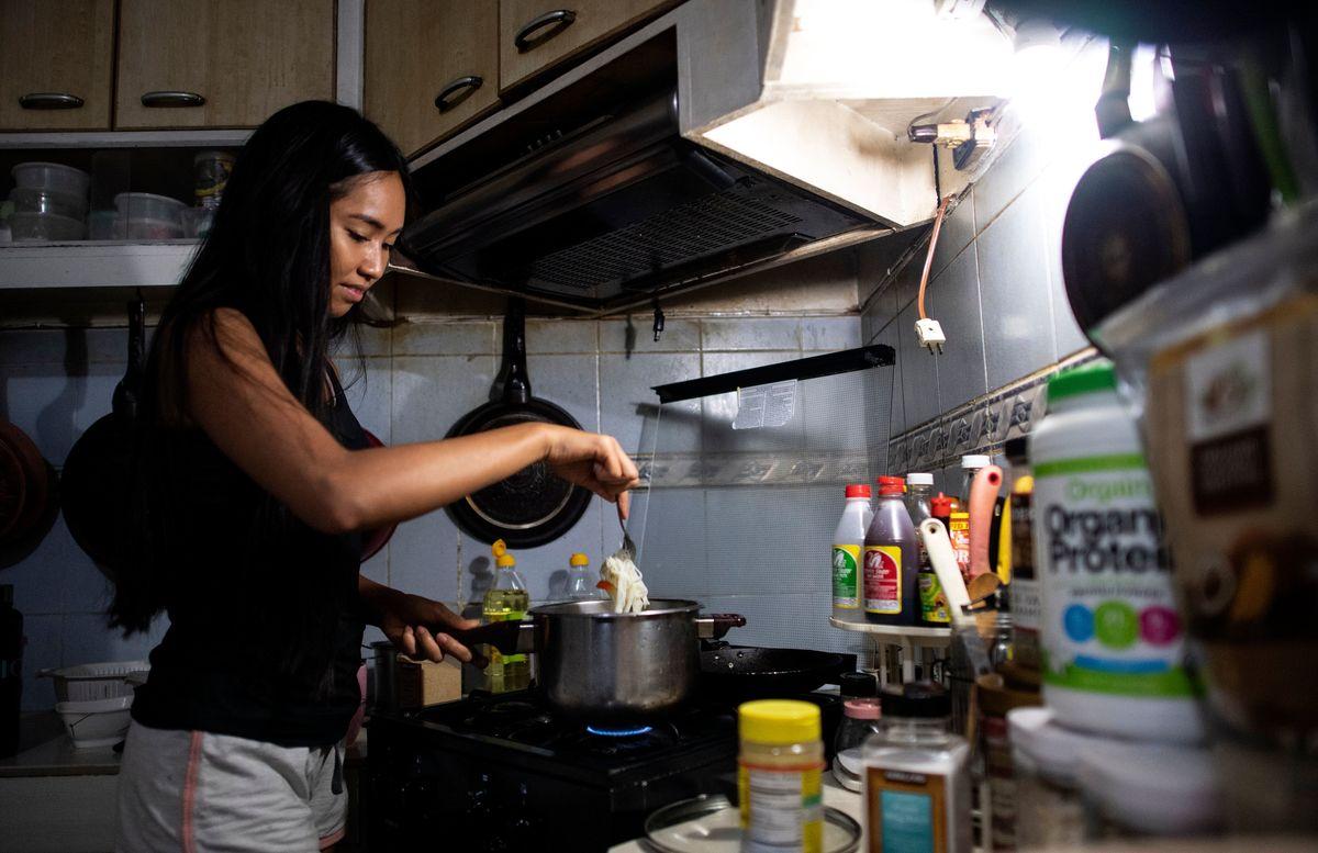 Aspiring beauty queen Monica Joelle Ortiz cooks lunch in her house in Manila.
