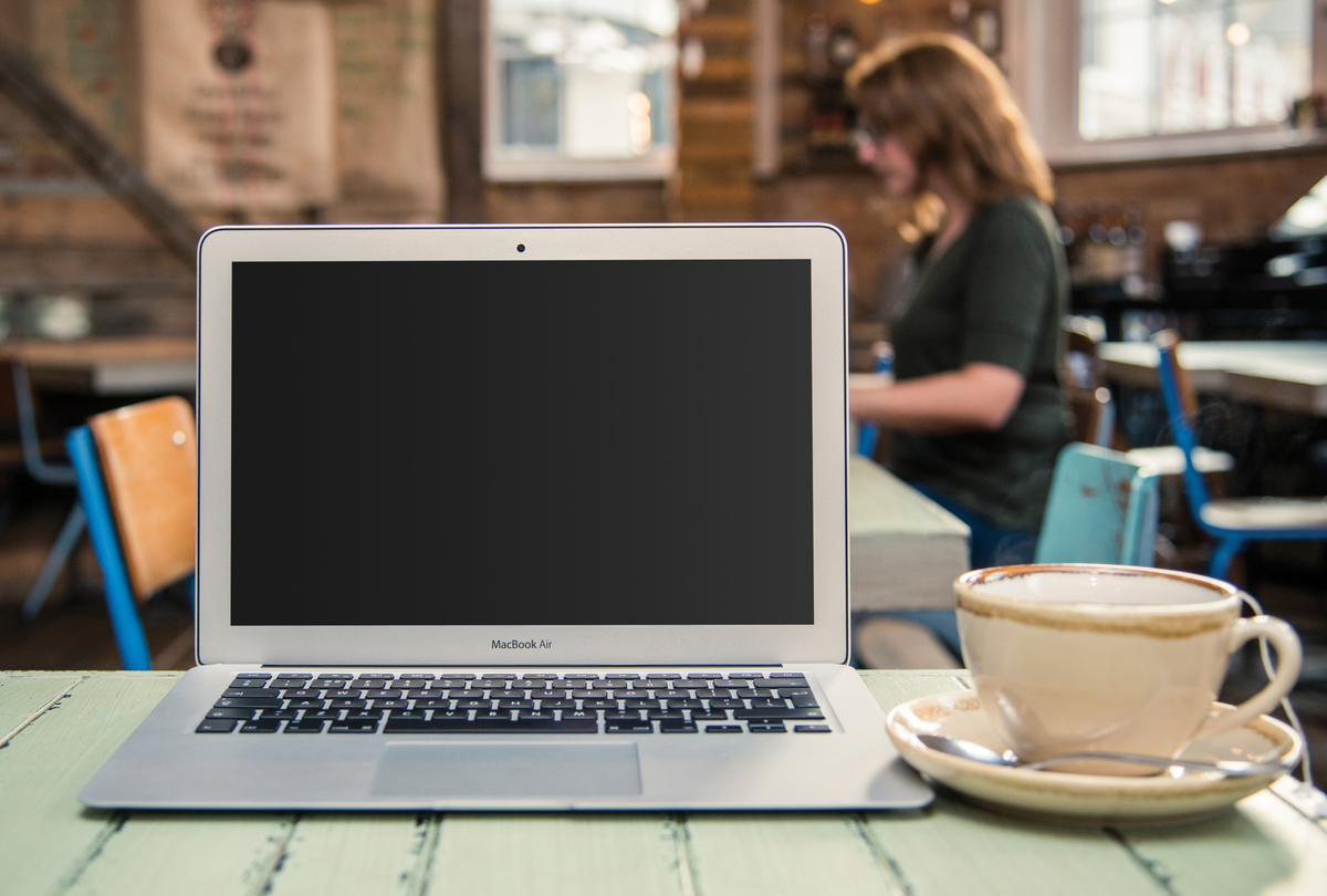 An Apple MacBook Air laptop computer is on the table of a coffee shop