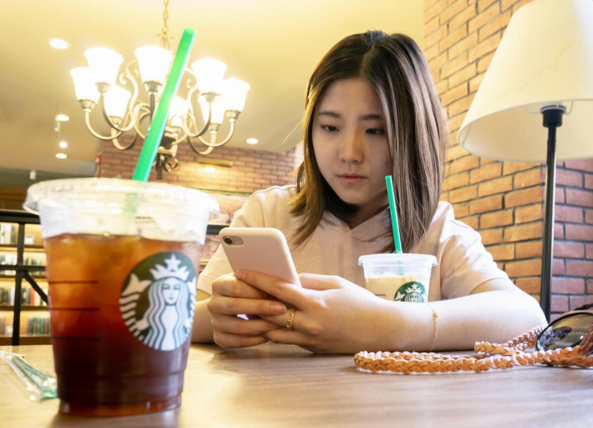 A girl is drinking ice coffee in a Starbucks coffee shop.