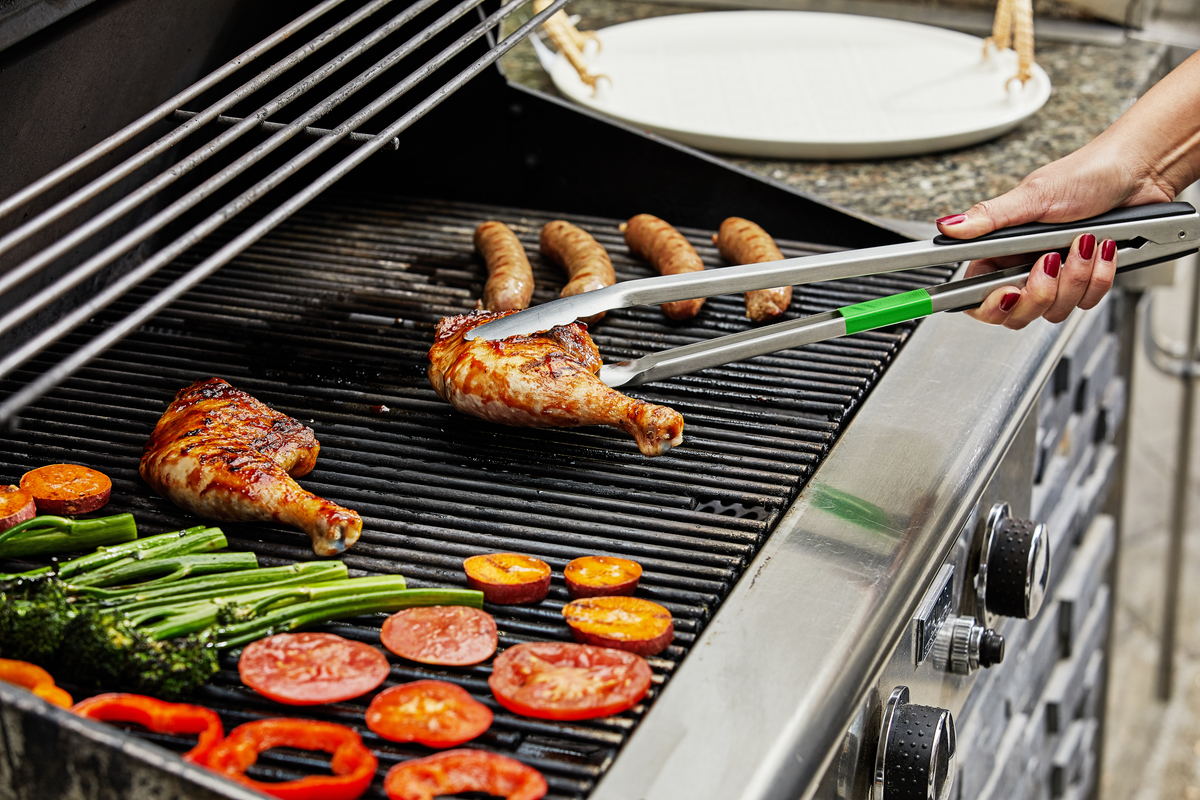 Person grills chicken, sausage, and vegetables