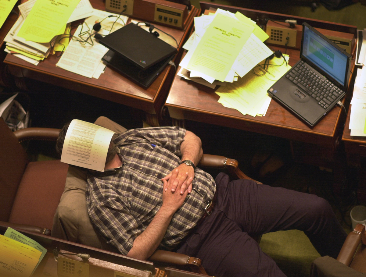 Man sleeps at his desk with a piece of paper over his face.