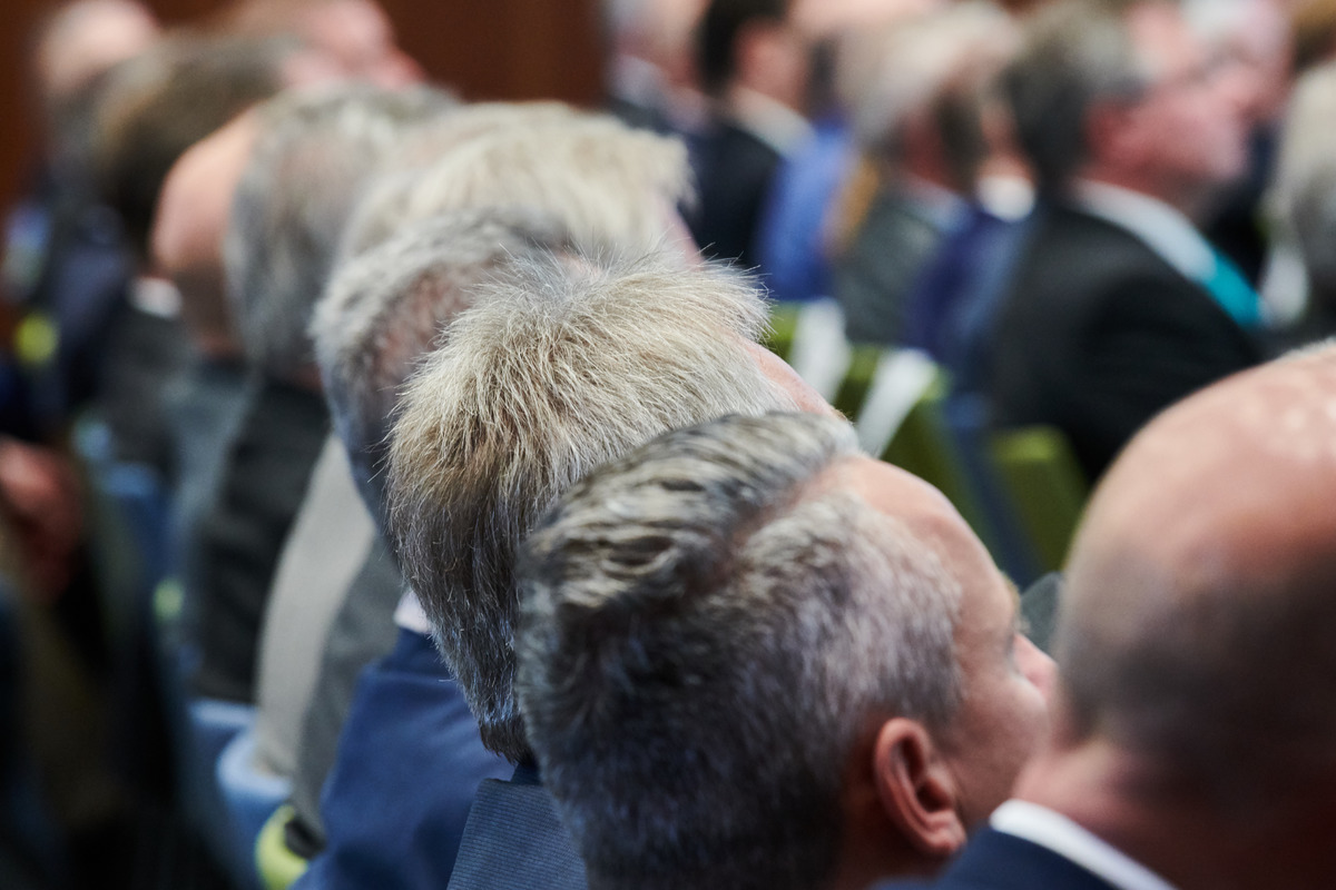 Middle-aged men and grey hair sit in an audience.
