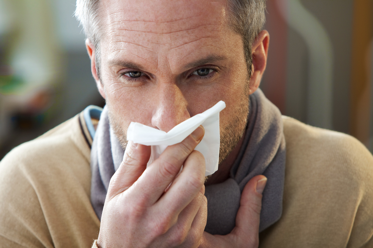 Man with Rhinitis blows his nose