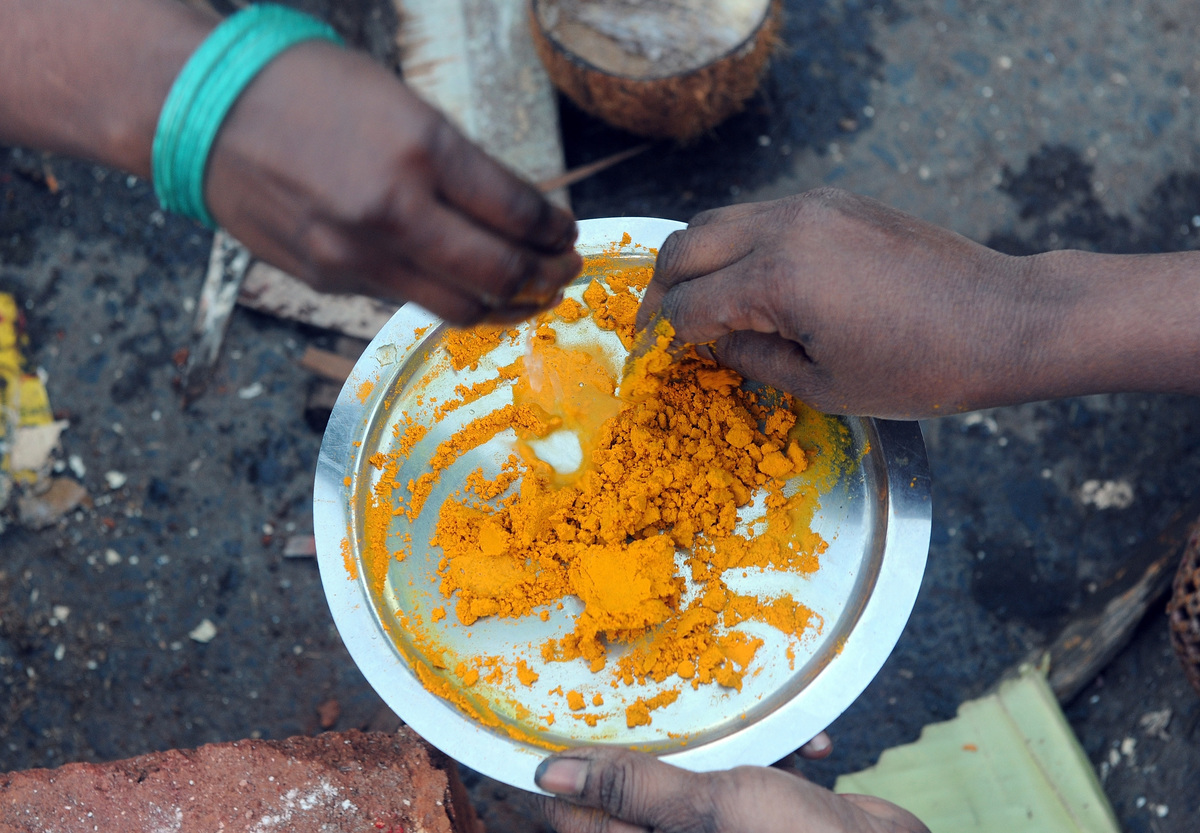 Indian Hindu devotees prepare a paste from turmeric powder during a community function
