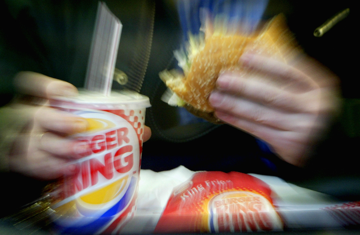 A man eats his lunch quickly at a Burger King restaurant