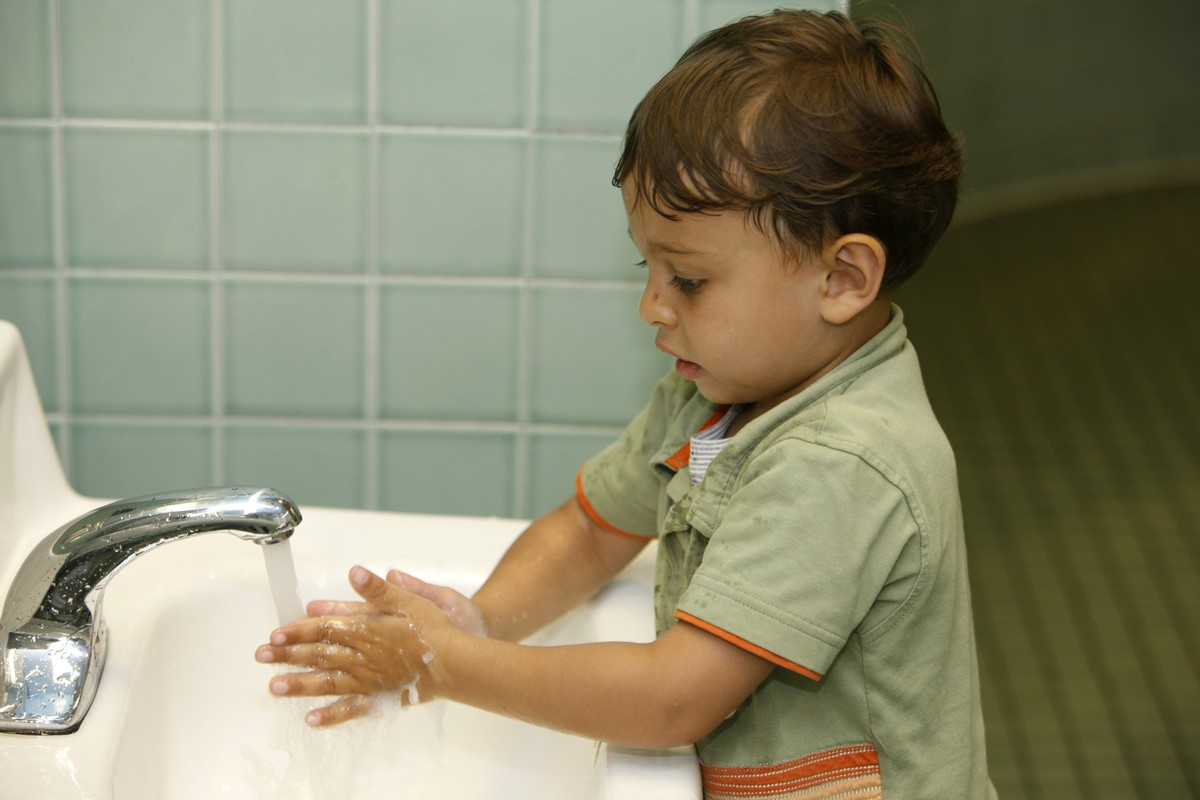 Boy washes his hands in a public restroom.