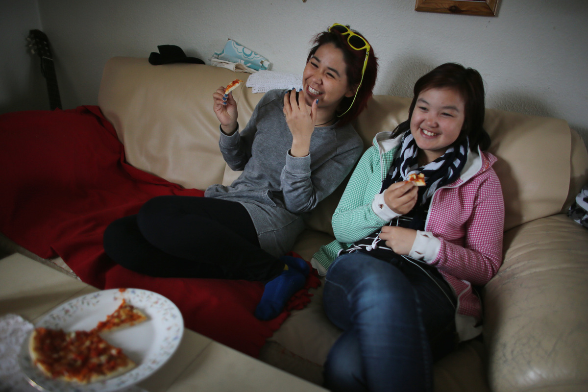 Two friends eat pizza as they watch TV  on the couch.