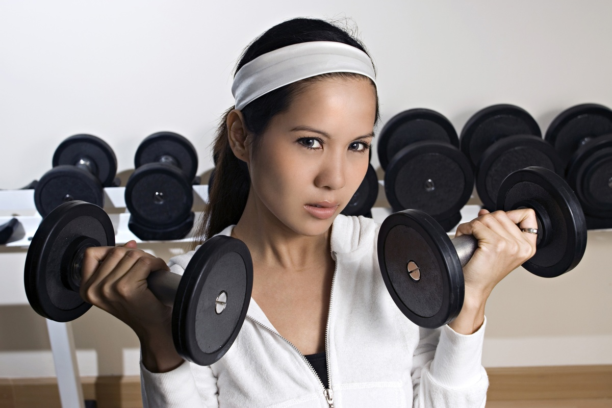 A young Asian girl works out in a gym.