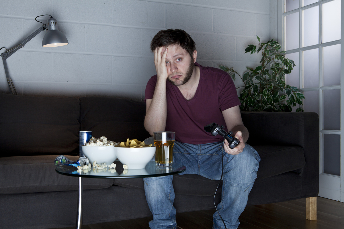A young man with a sleepy expression playing Sony PlayStation 2 video games on a sofa alongside a table of snacks