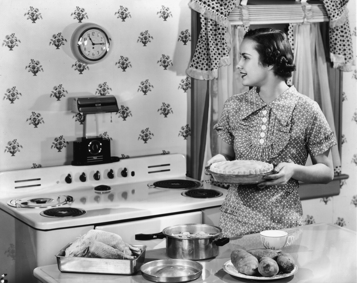 A housewife holds an unbaked pie while looking at a wall clock in a kitchen.