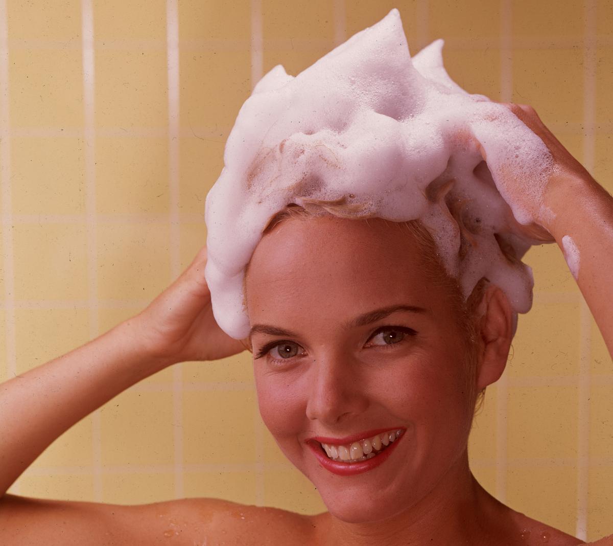 A woman lathers shampoo into her hair circa 1960