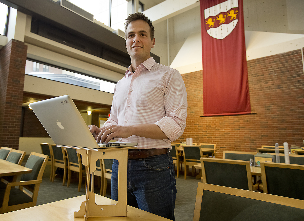 Luke Leafgren works on his portable standing desk invention in Harvard's Mather House dining hall