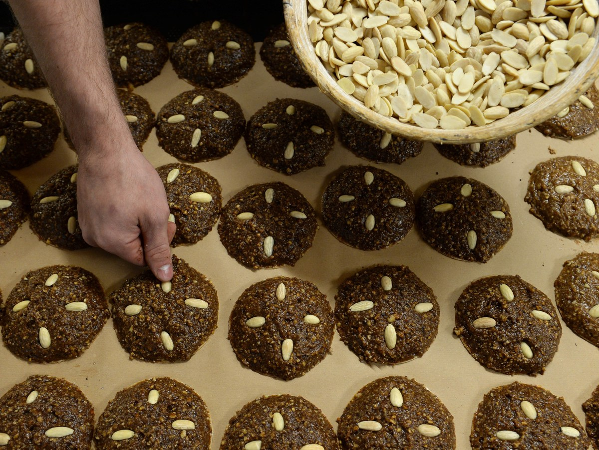 A baker sets almonds over typical Nuremberger ginger breads in a bakery
