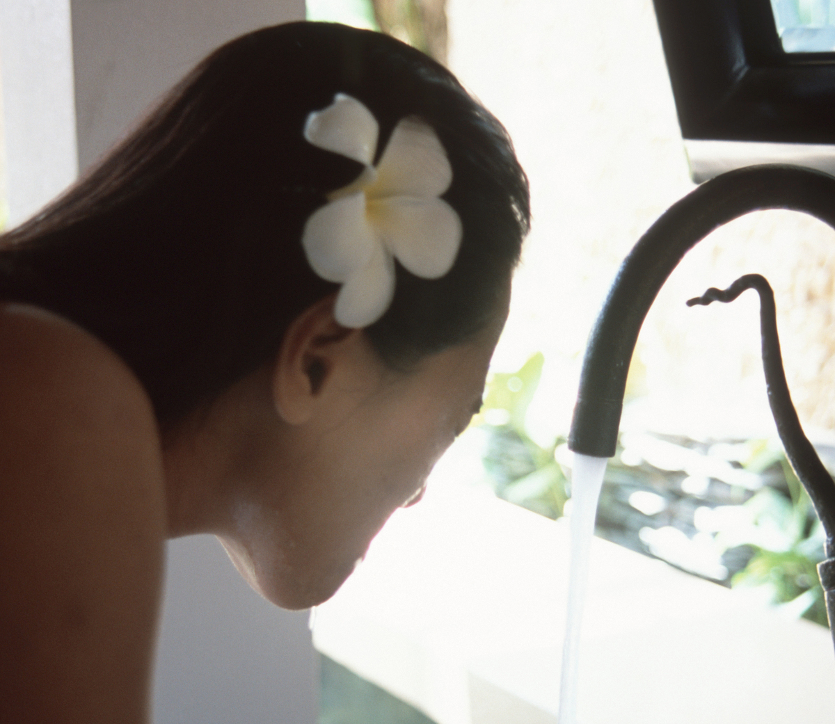 A woman washes her face at the Marriott's Mandara Spa.