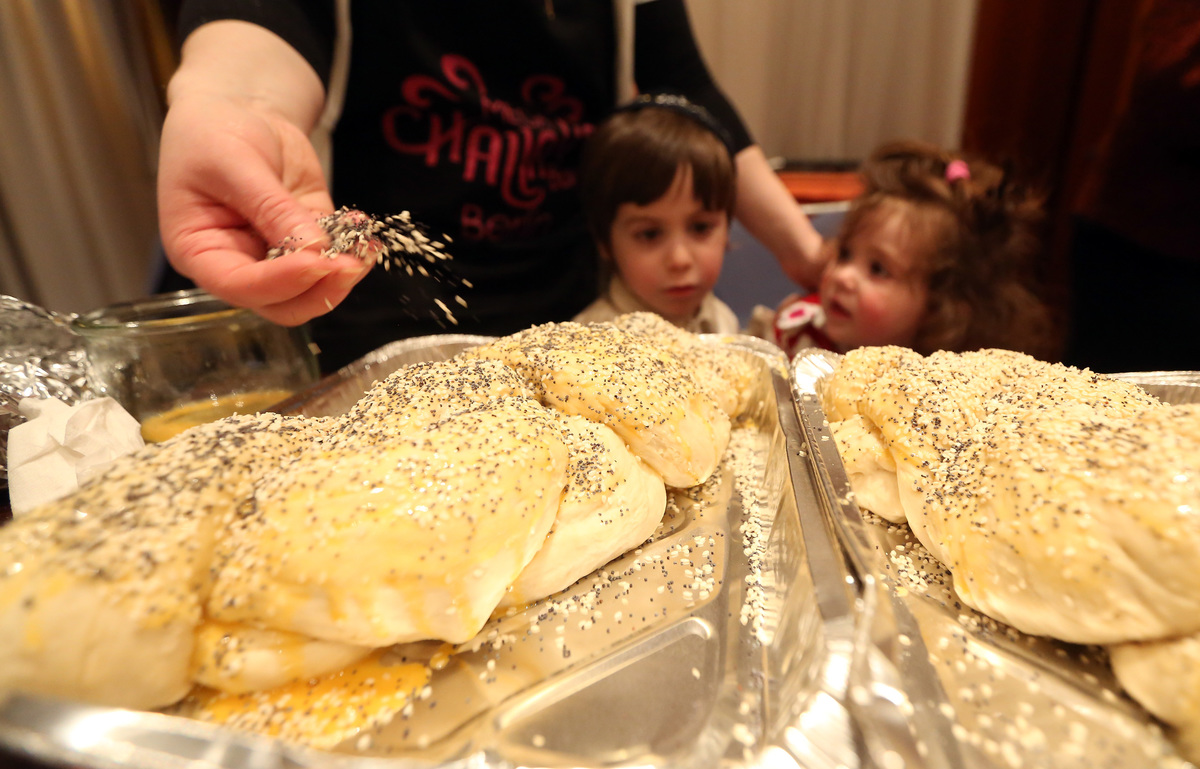 A participant sprinkles sesame seeds on a challah during the Mega Challah Bake