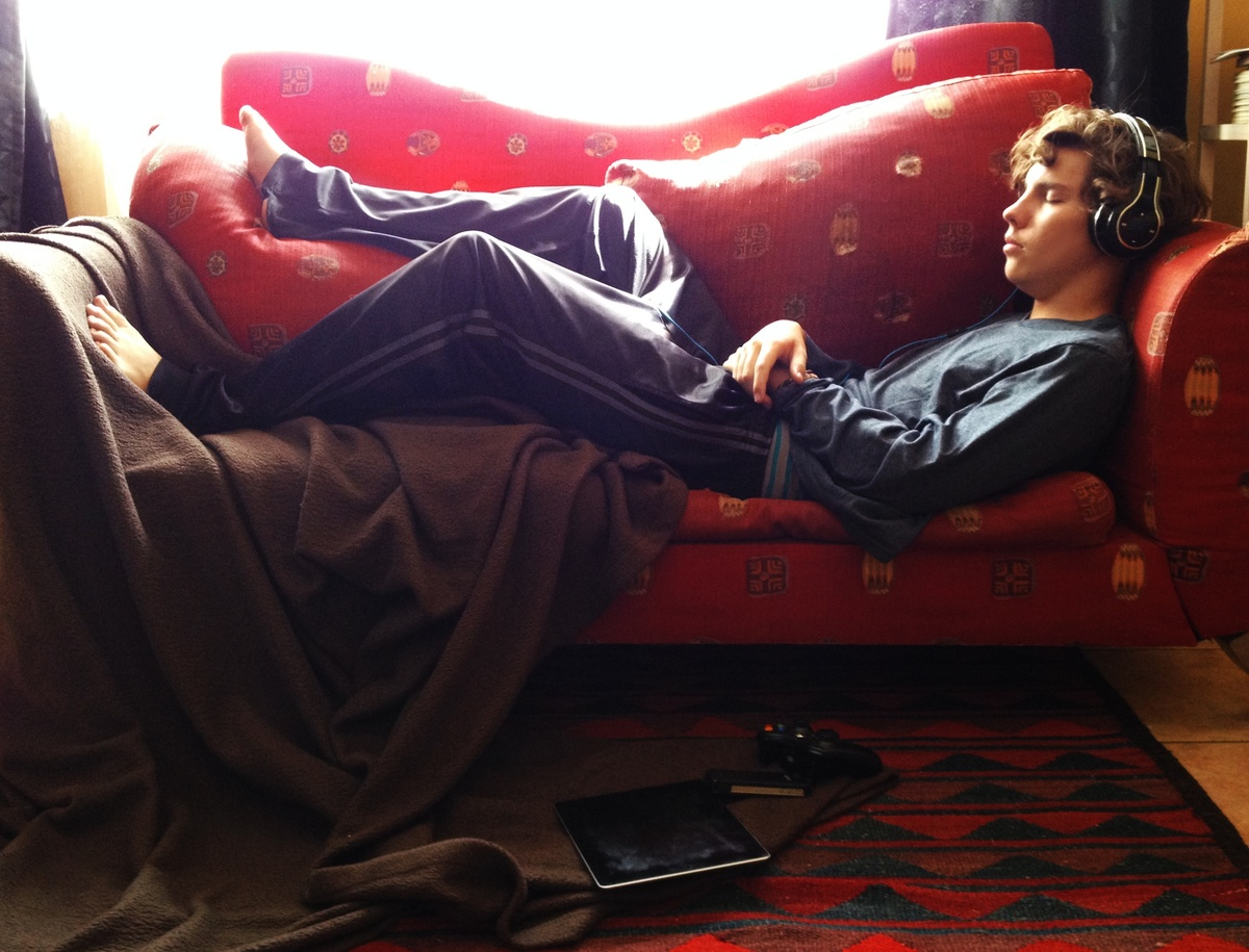 A young man dozing on a red couch listening to music.