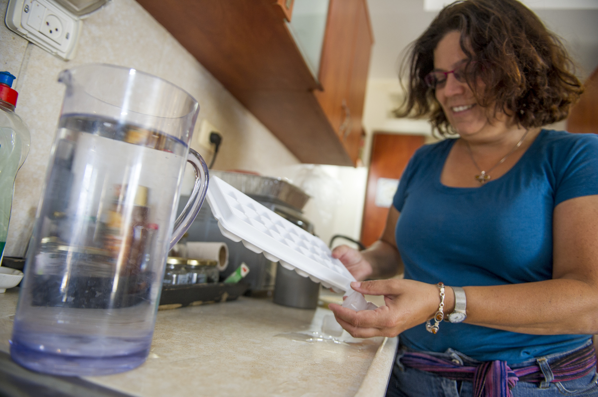 American born Israeli, Jackie Bitensky, gathers ice cubes for drinking water