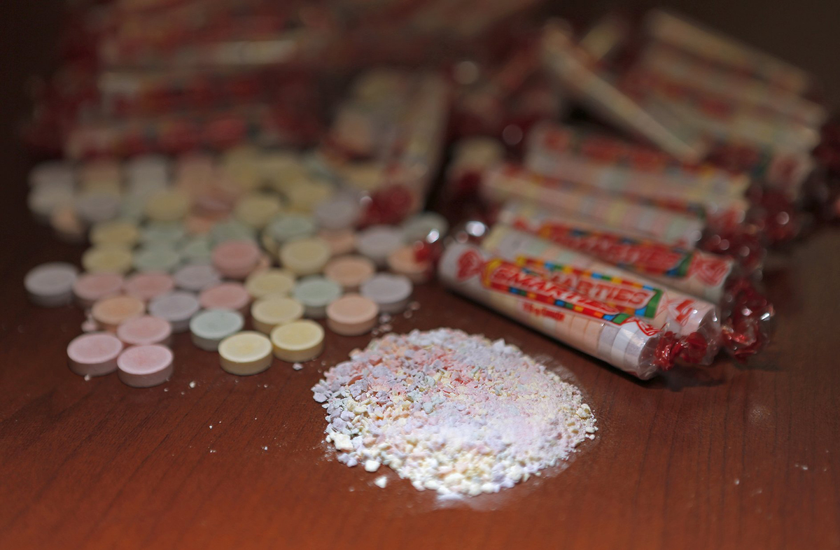 Crushed smarties lay in front of Smarties packages.
