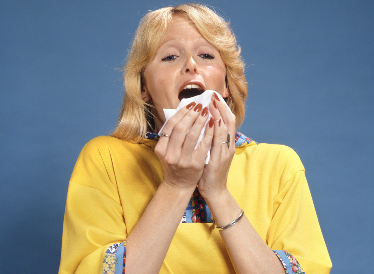 1980s Blonde woman sneezes into a tissue.