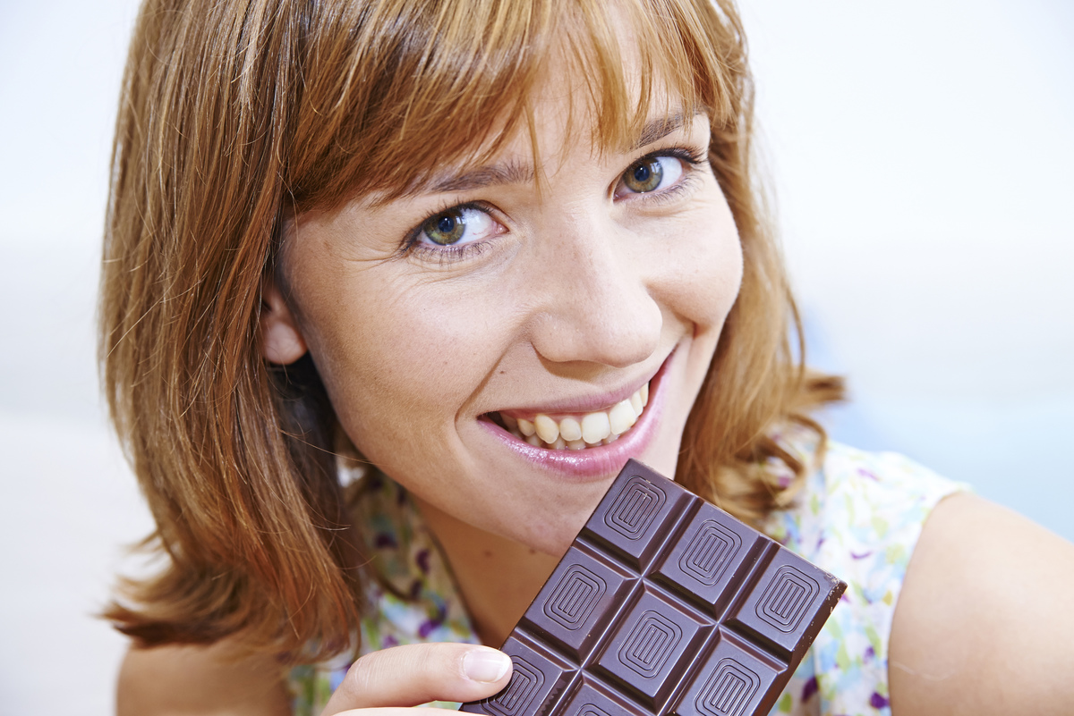 Woman eating a chocolate bar.