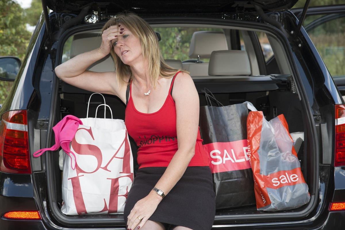 An exhausted female shopper rubs her head while sitting with her shopping bags.