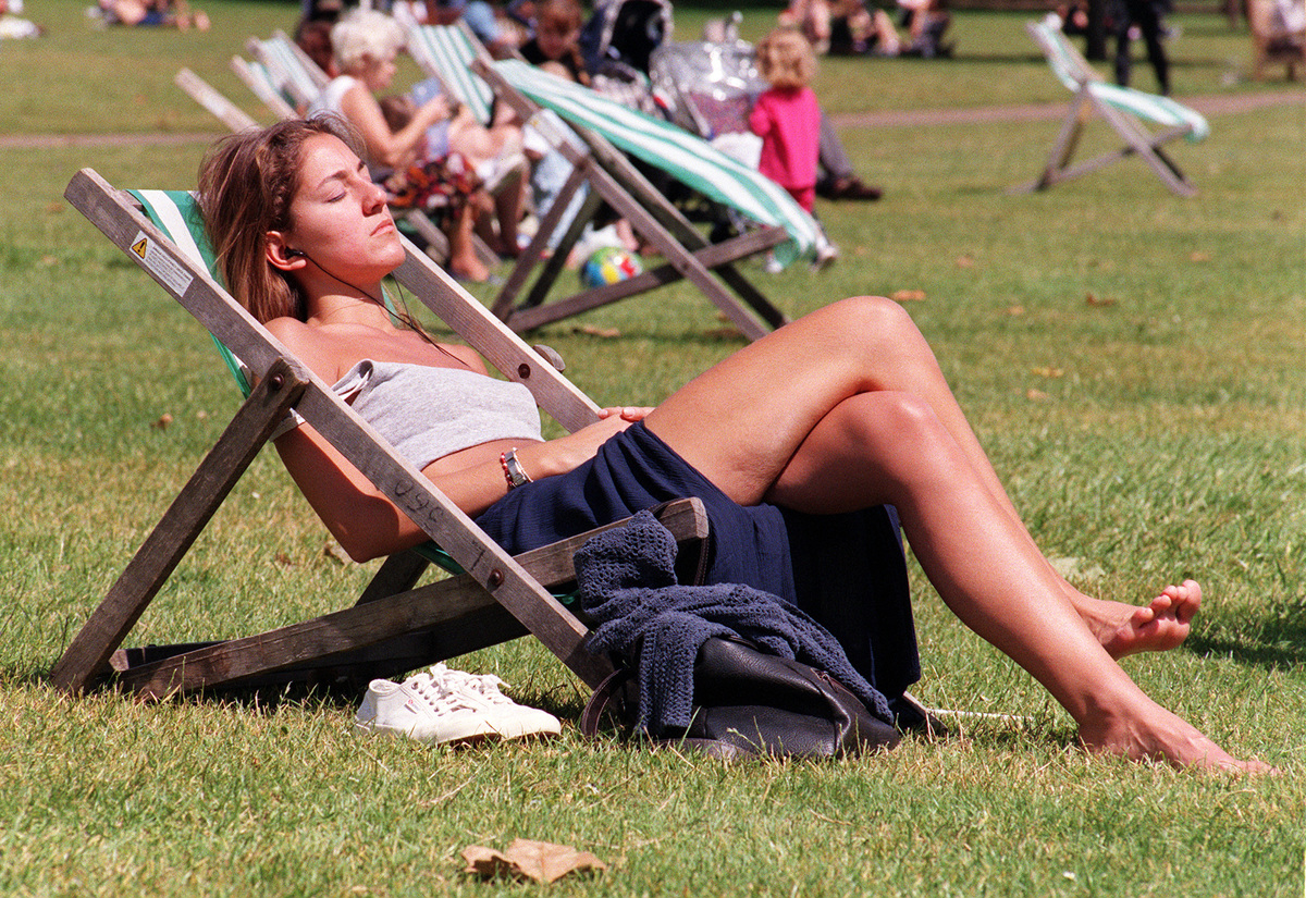 Sunbathers relax on lawn chairs at St. James's Park