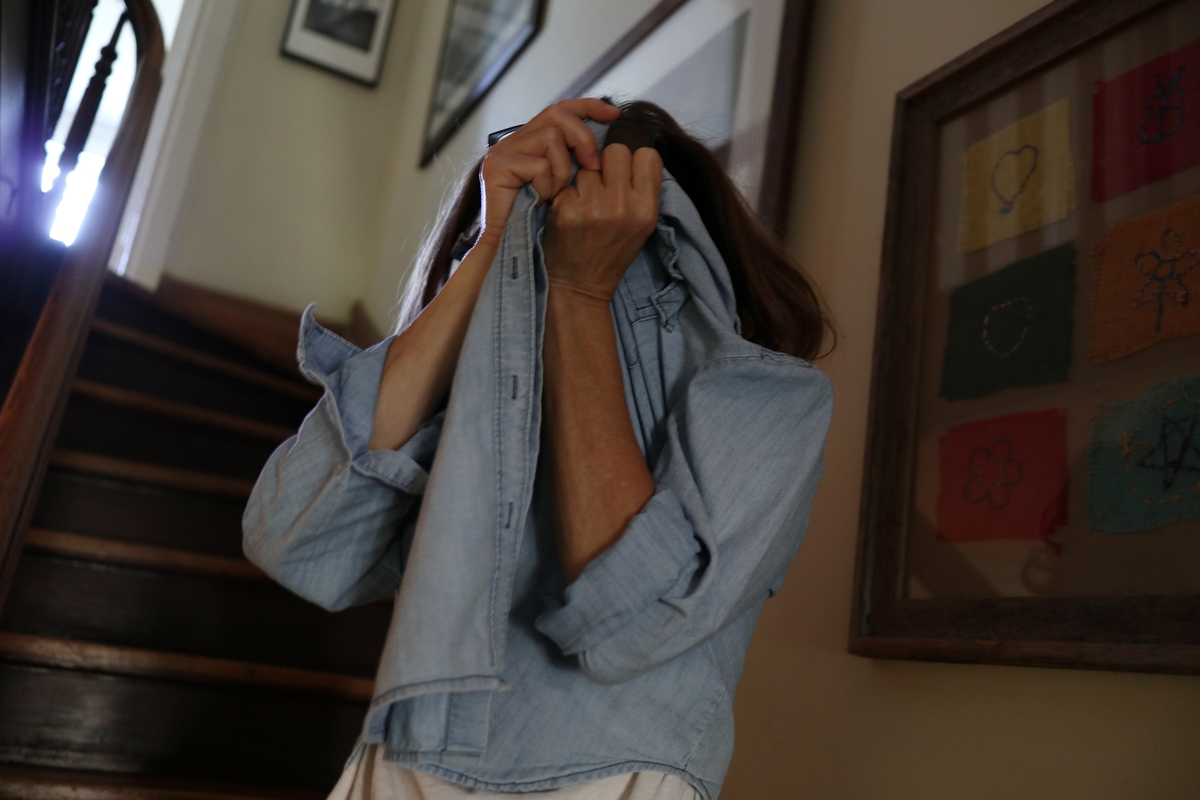 A woman covers her face during a difficult day managing as a mother and working full time
