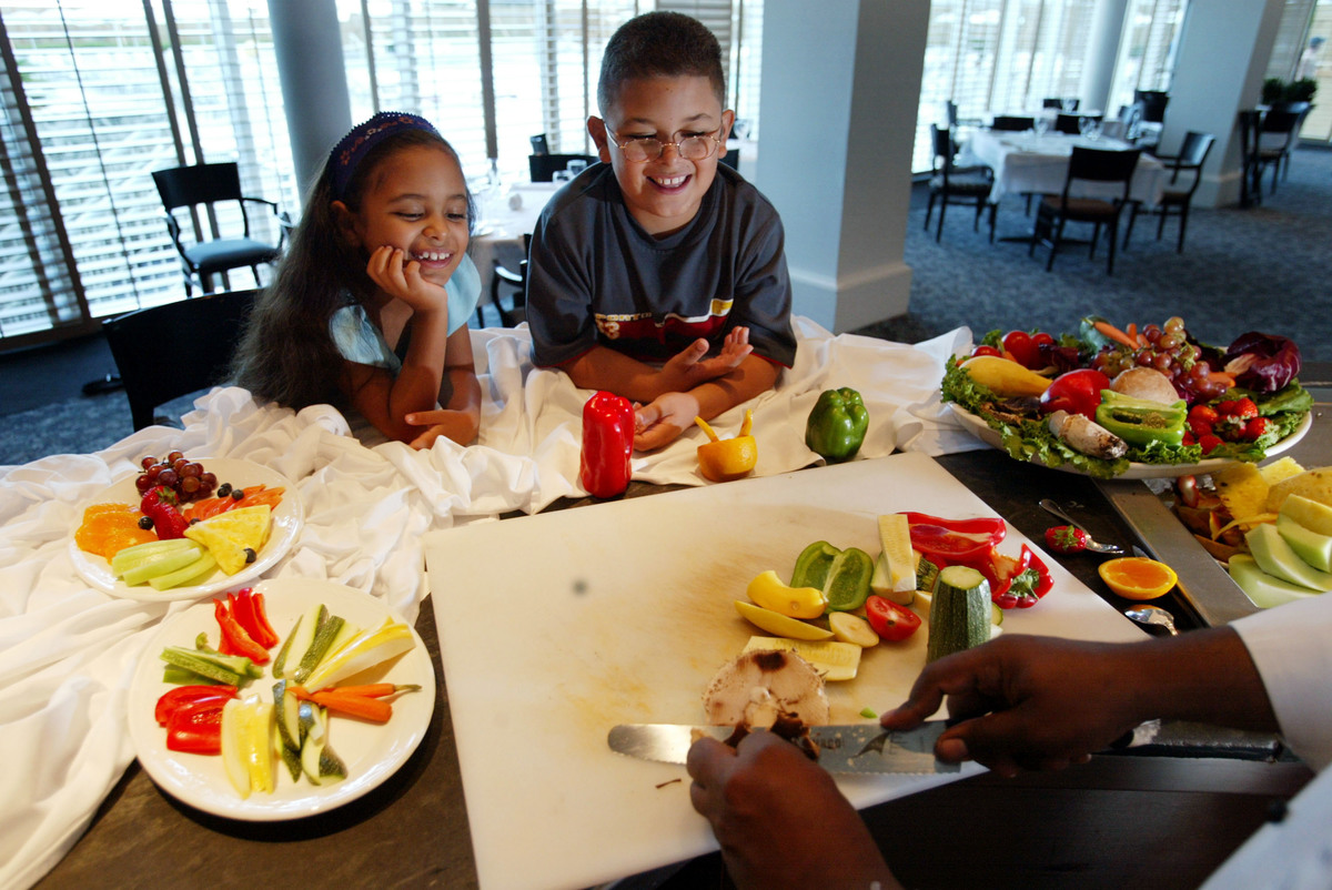 Sheriss Chacon and her brother Shawn Chacon watch as Eden Roc Renaissance Resort & Spa chef Patrick Barthelemy makes a healthy snack