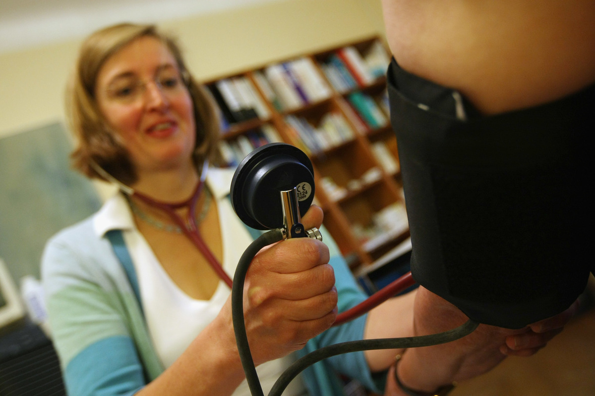 A family doctor measures an elderly patient's blood pressure at her office