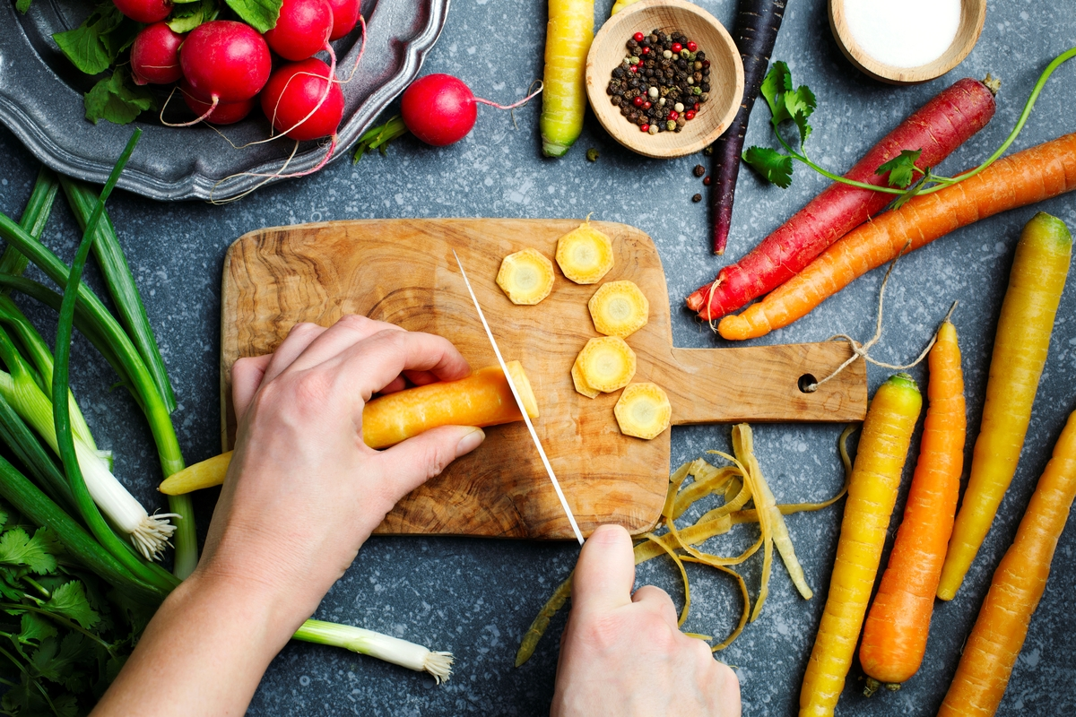 Woman hands cutting carrots on wooden board and fresh spring vegetables for vegetarian cooking on the table