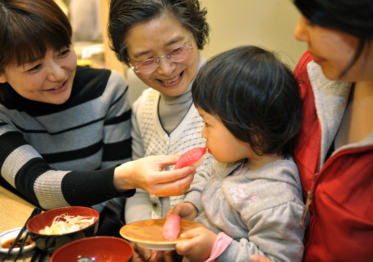 A little girl eats bluefin tuna sushi at a sushi restaurant in Yokohama city, suburban Tokyo.